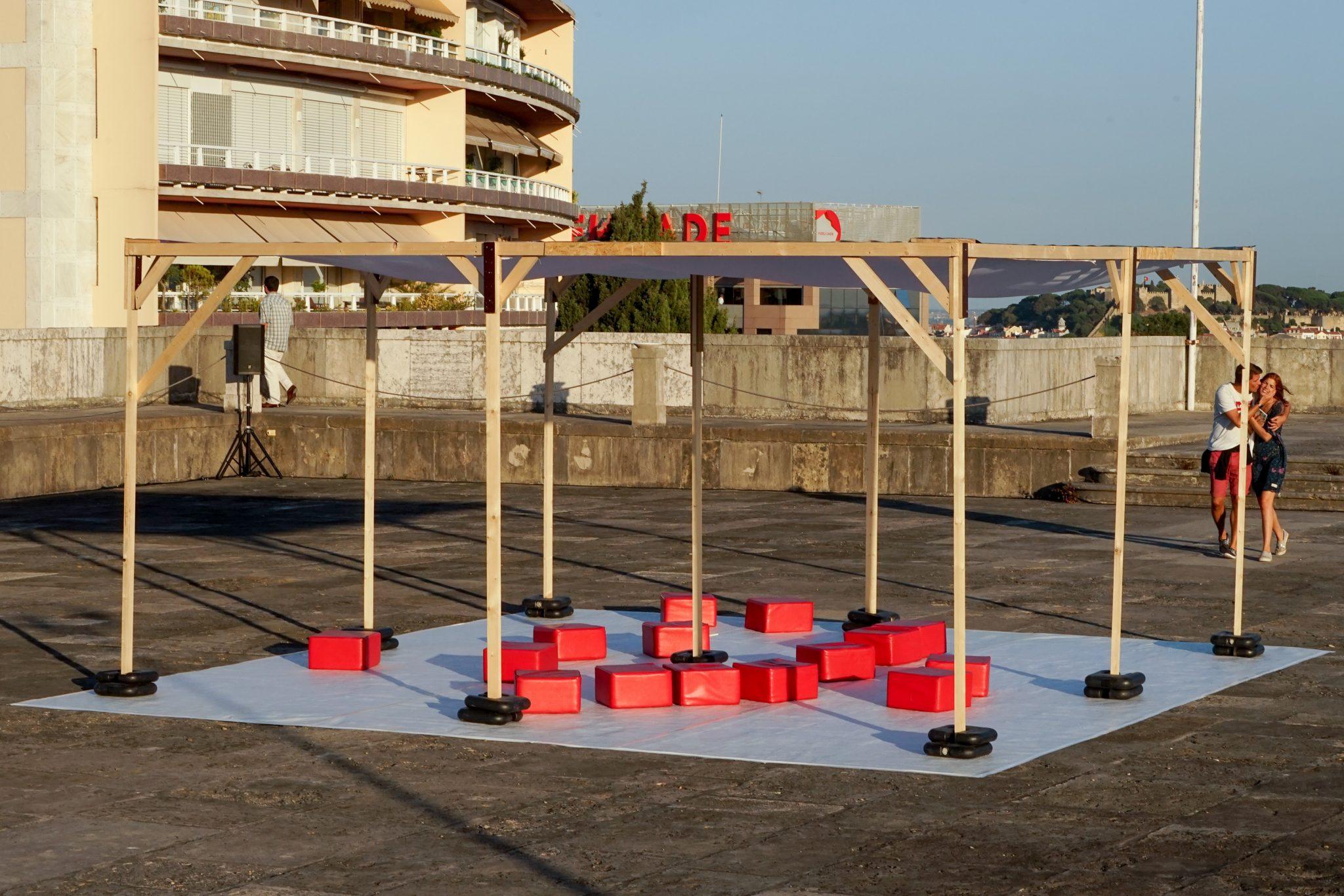 Terraço exterior, com estrutura de madeira presa com pesos pretos em cima de uma lona branca. Em cima dessa lona estão cubos vermelhos