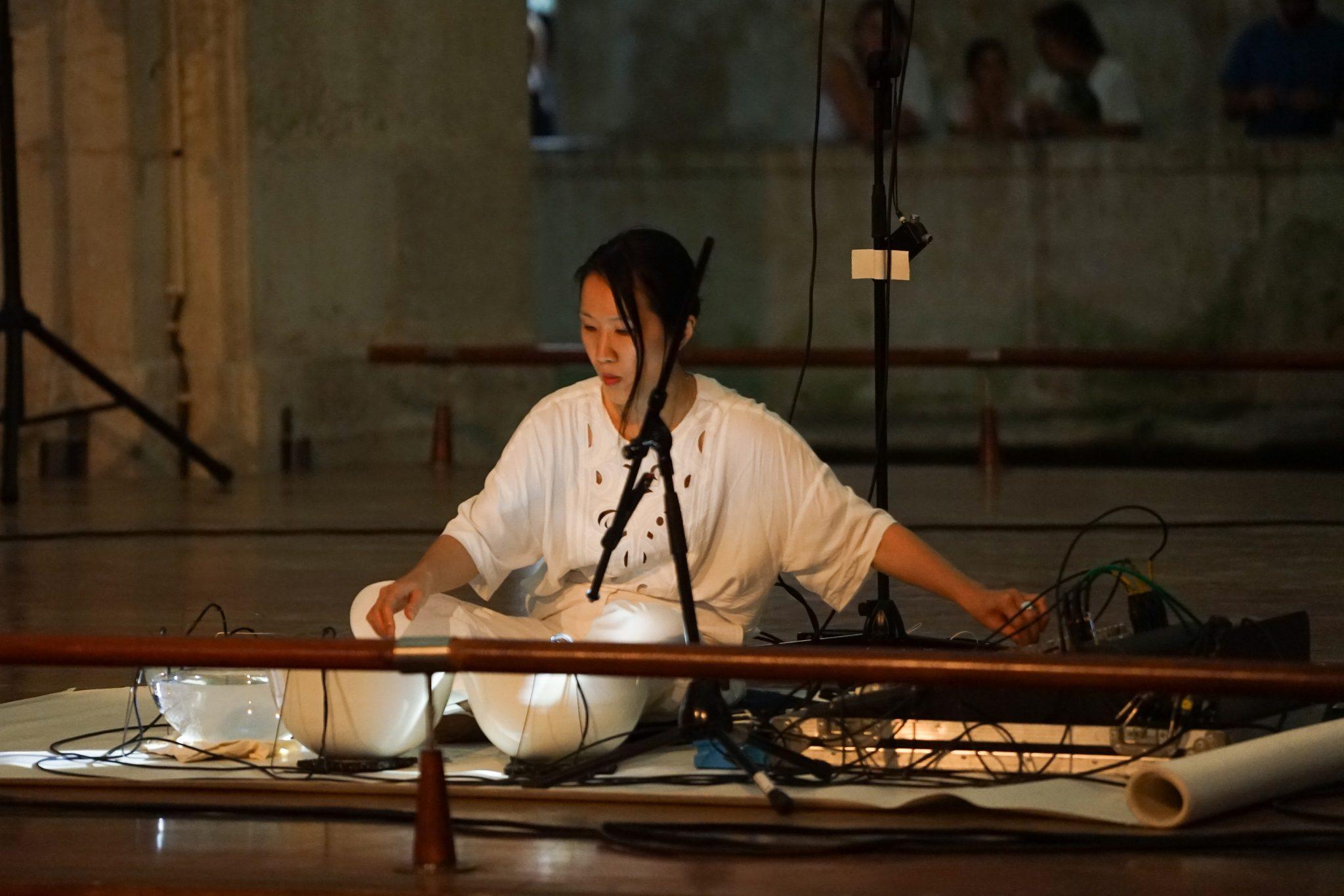 Mulher sentada, de frente para o observador, a mexer numa mesa de som
