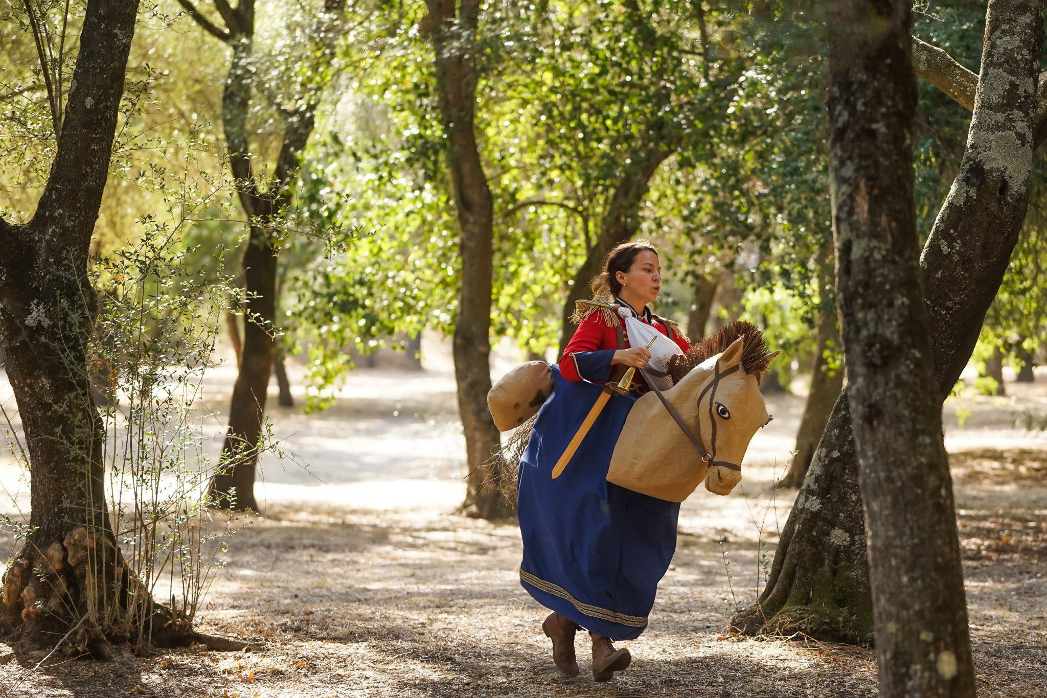 Mulher de frente para o observador, com casaco militar e espada de madeira, num cavalo feito com uma estrutura de pano, simulando o trote do cavalo