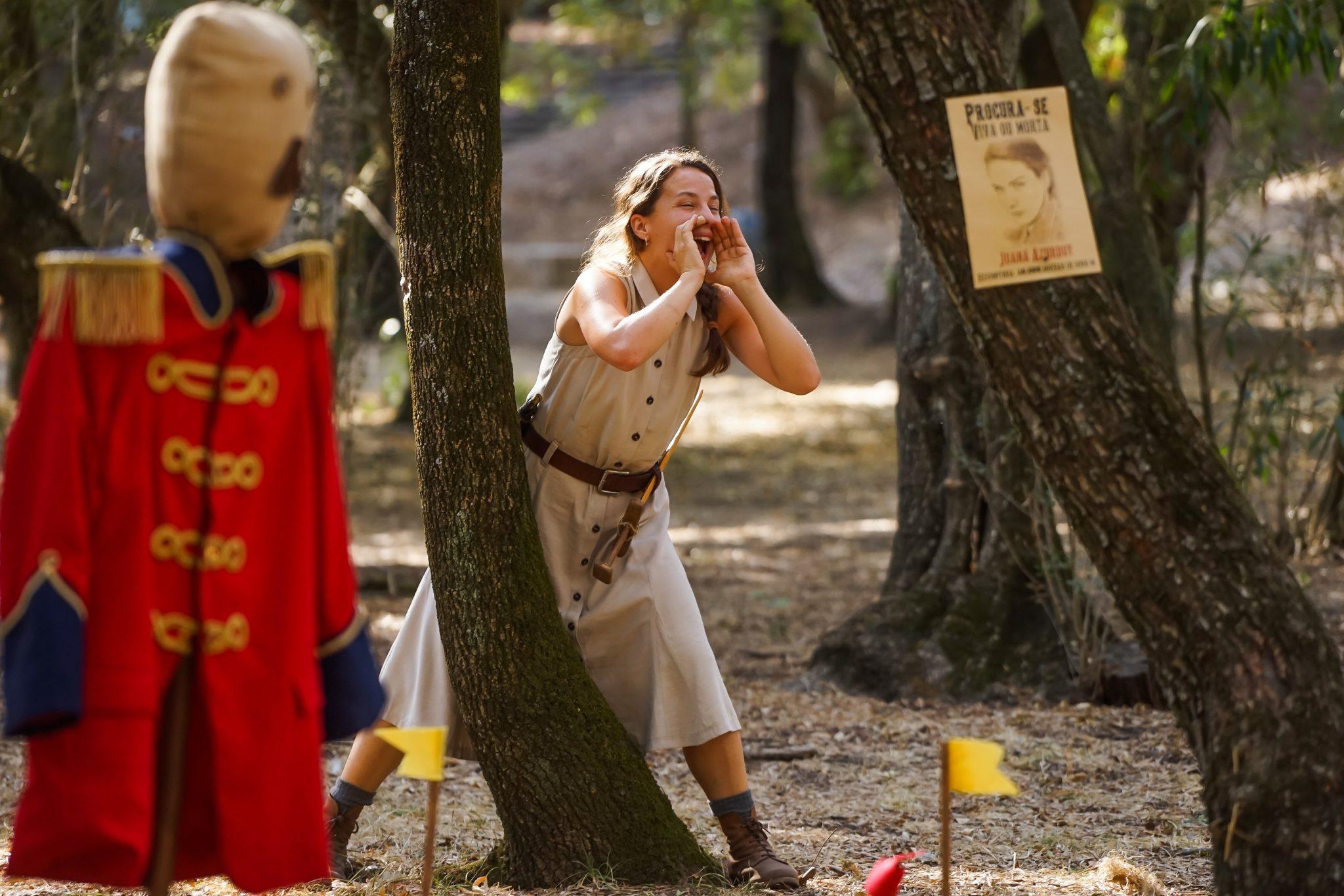 Mulher de frente para o observador a gritar com as mãos em concha à volta da boca