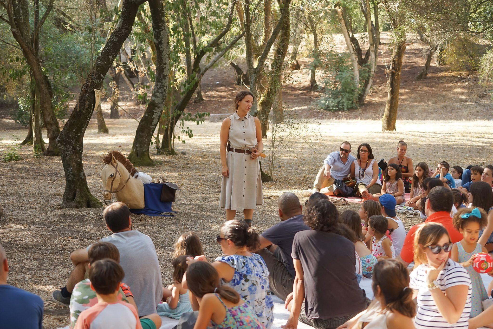 Grupo de crianças e adultos sentados em semi-círculo no chão de uma mata, de costas, de lado e de frente para o observador, a olhar para uma mulher de pé, de frente para o observador