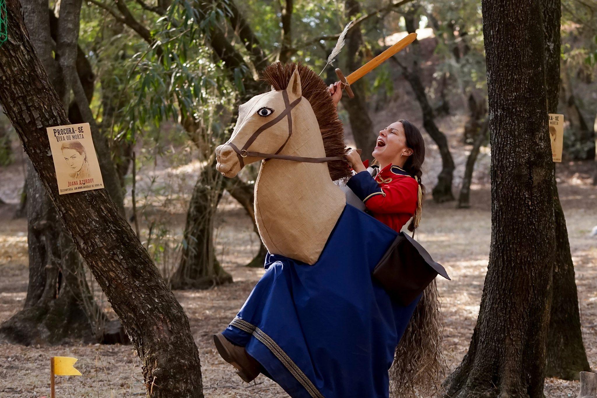 Mulher de frente para o observador, com casaco militar e espada de madeira, num cavalo feito com uma estrutura de pano