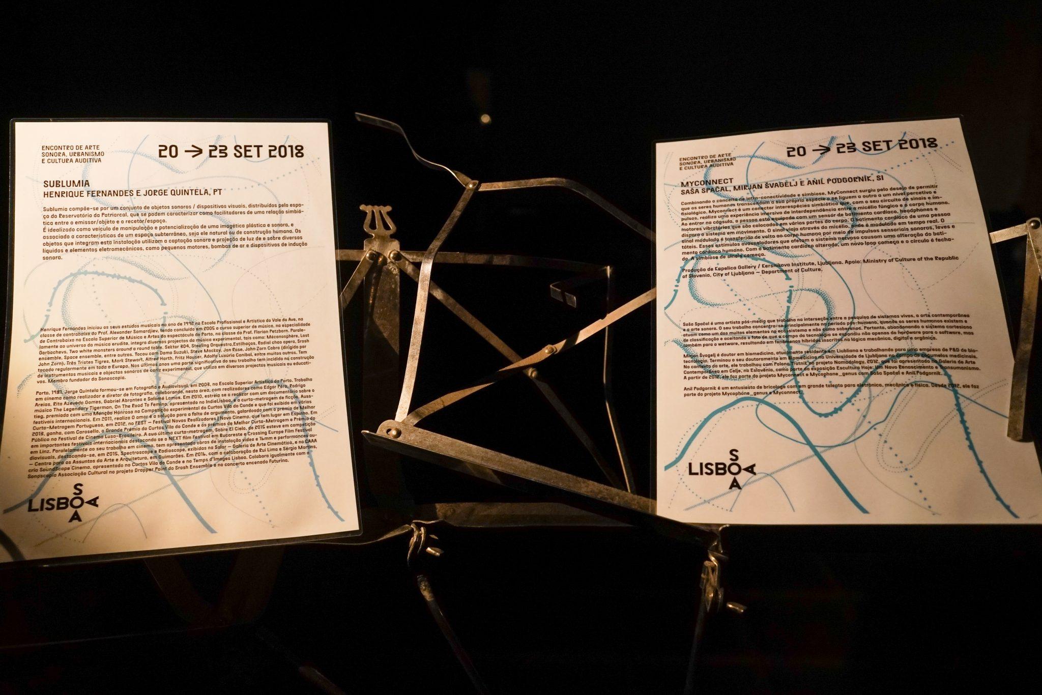 Suporte de pauta com duas folhas com textos descritivos das exposições no reservatório
