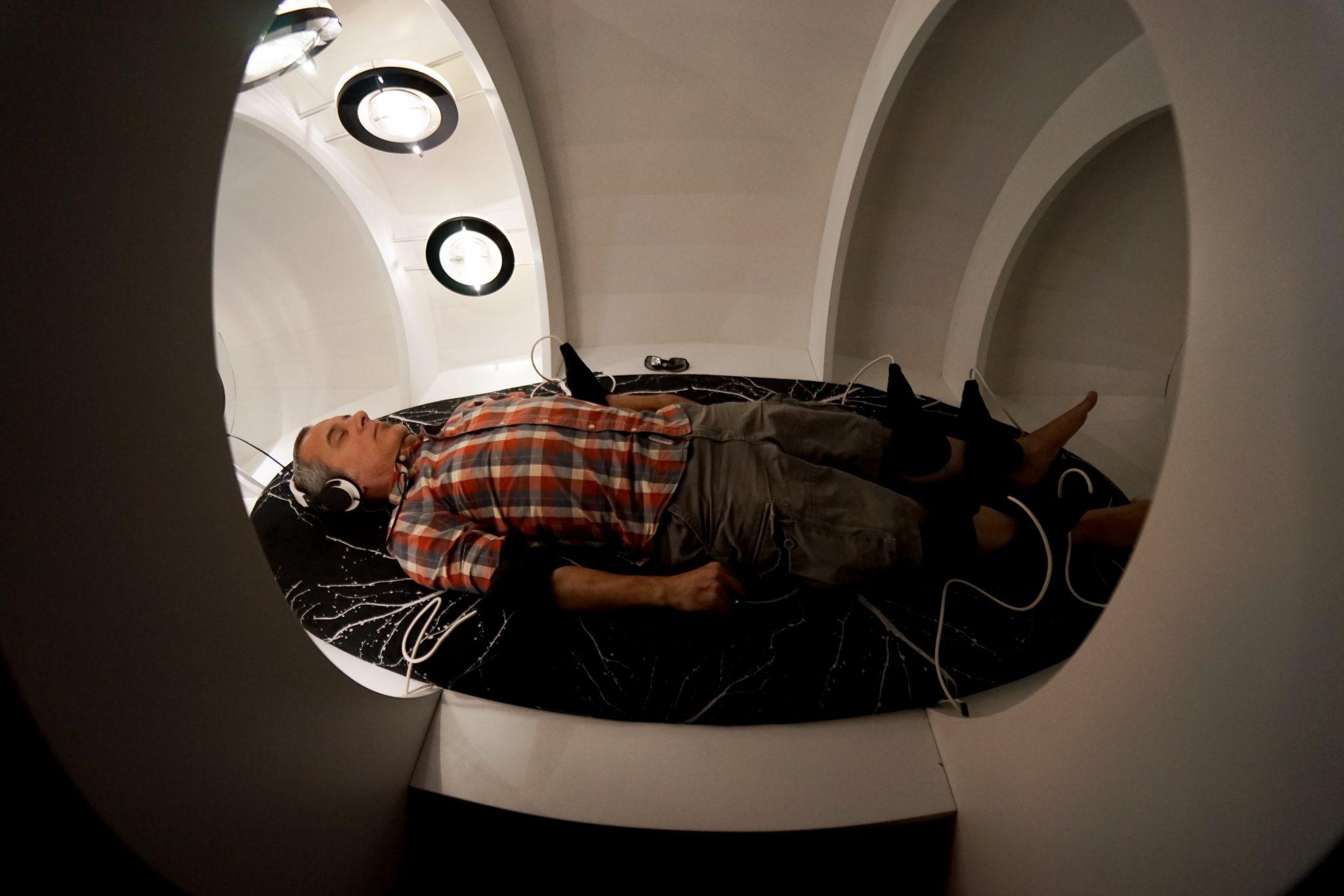 Homem deitado, vestido, descalço, com vários fios ligados ao corpo, dentro de uma cápsula