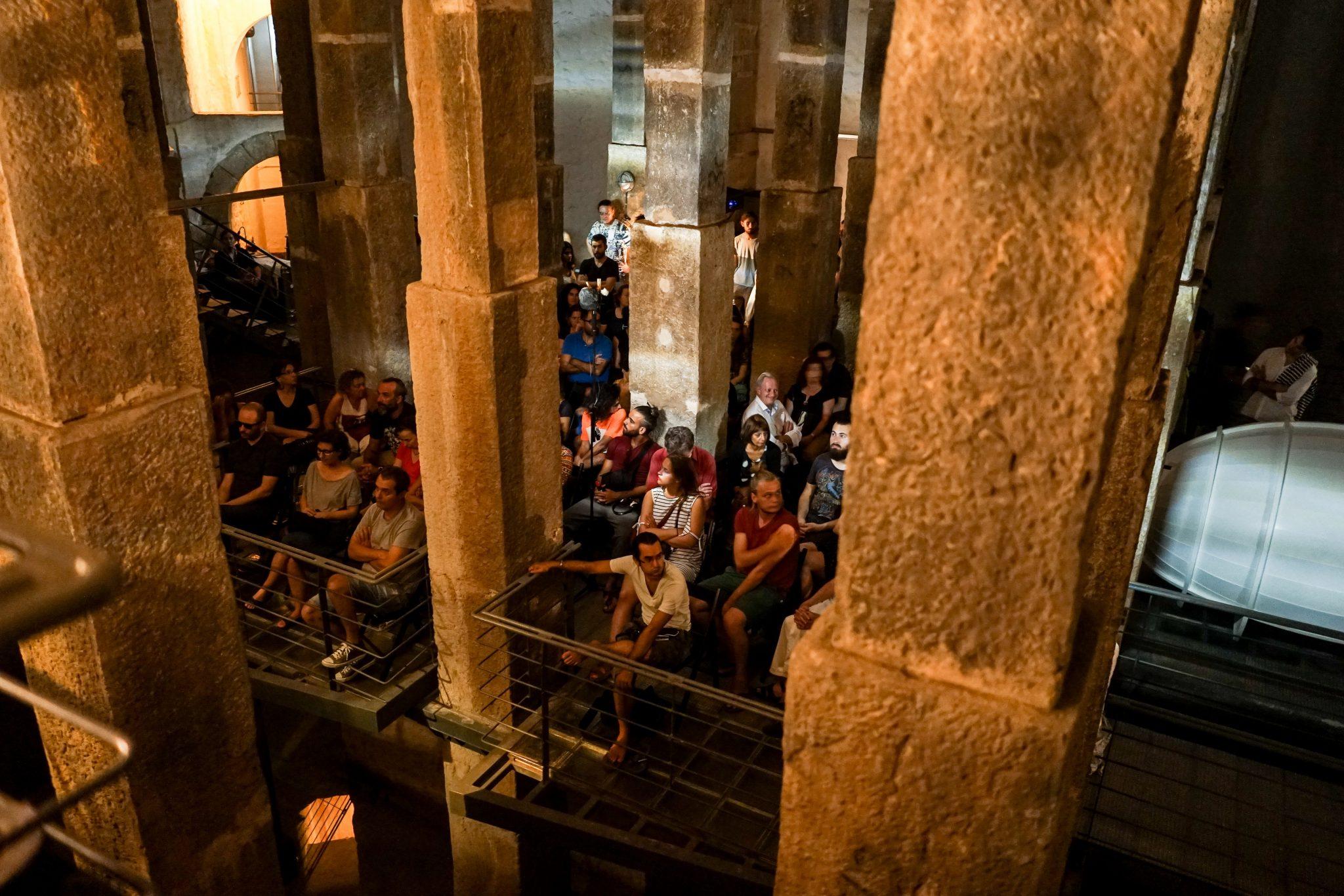 Grupo de pessoas sentadas de frente para o observador, entre as colunas do reservatório