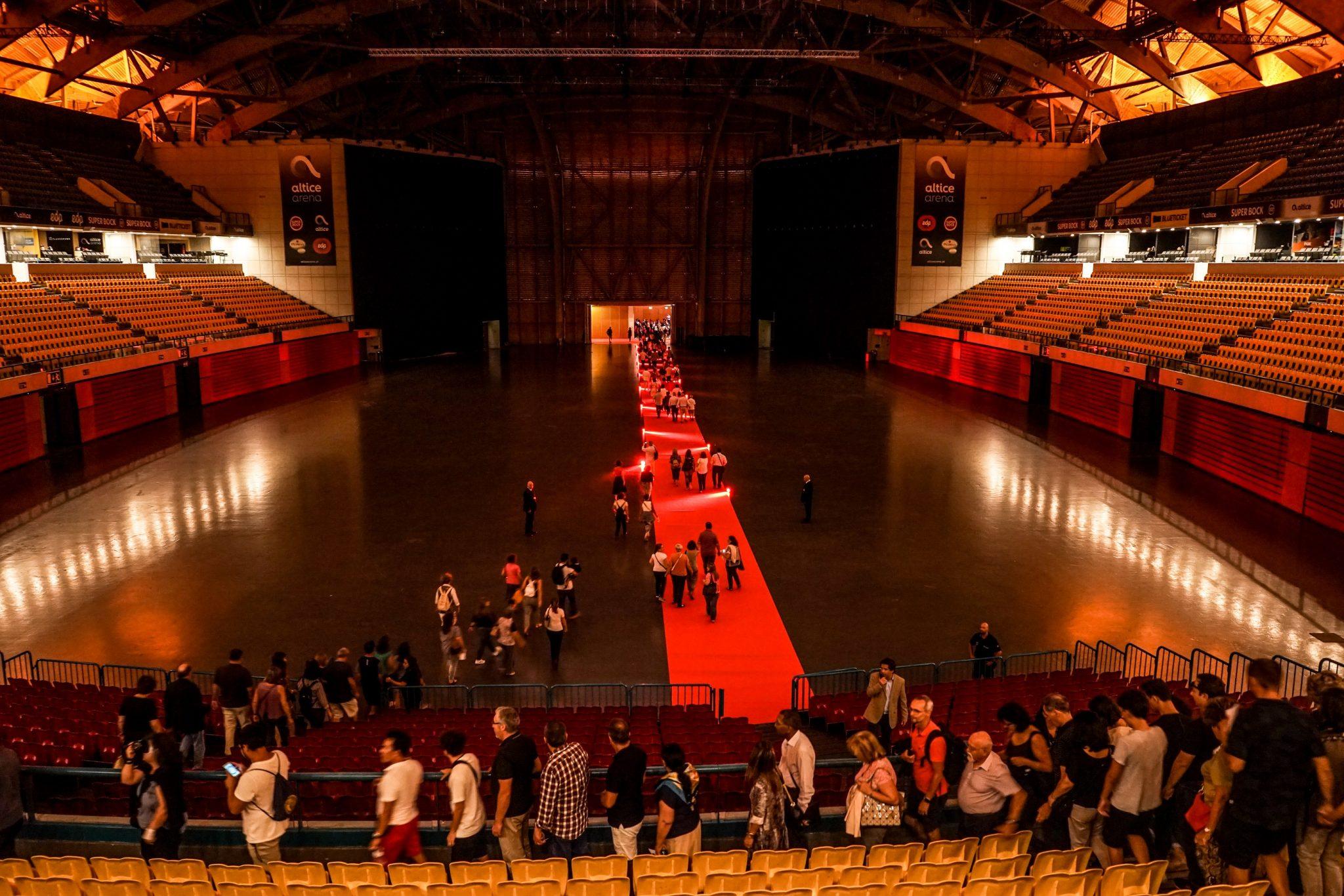 Interior do Pavilhão Atlântico, com plateias vazias e várias pessoas a descerem a escadaria e a atravessarem a sala
