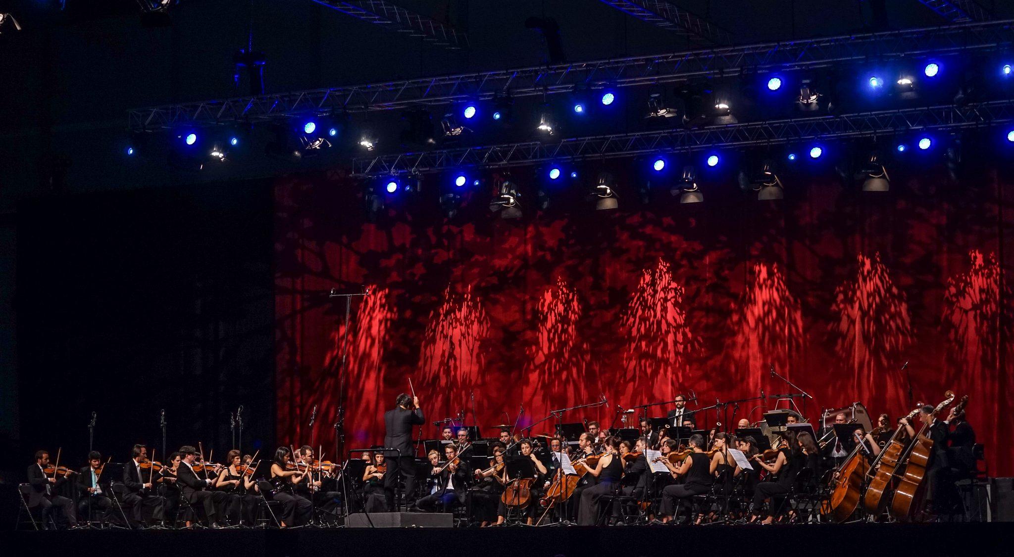 Músicos e maestro em palco durante concerto
