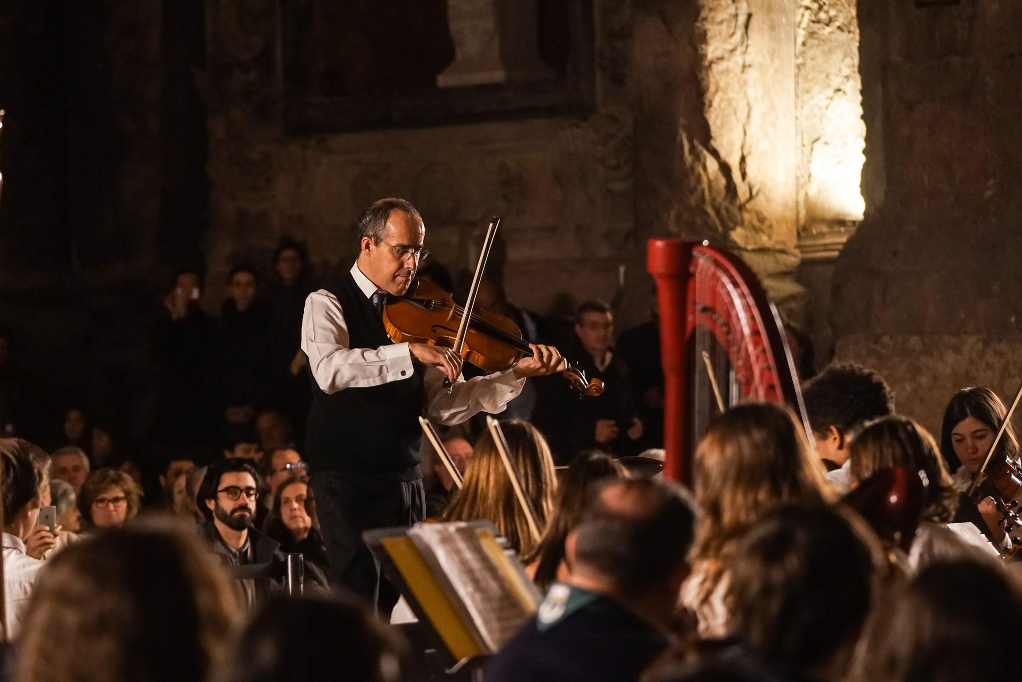 Homem de pé a tocar violino