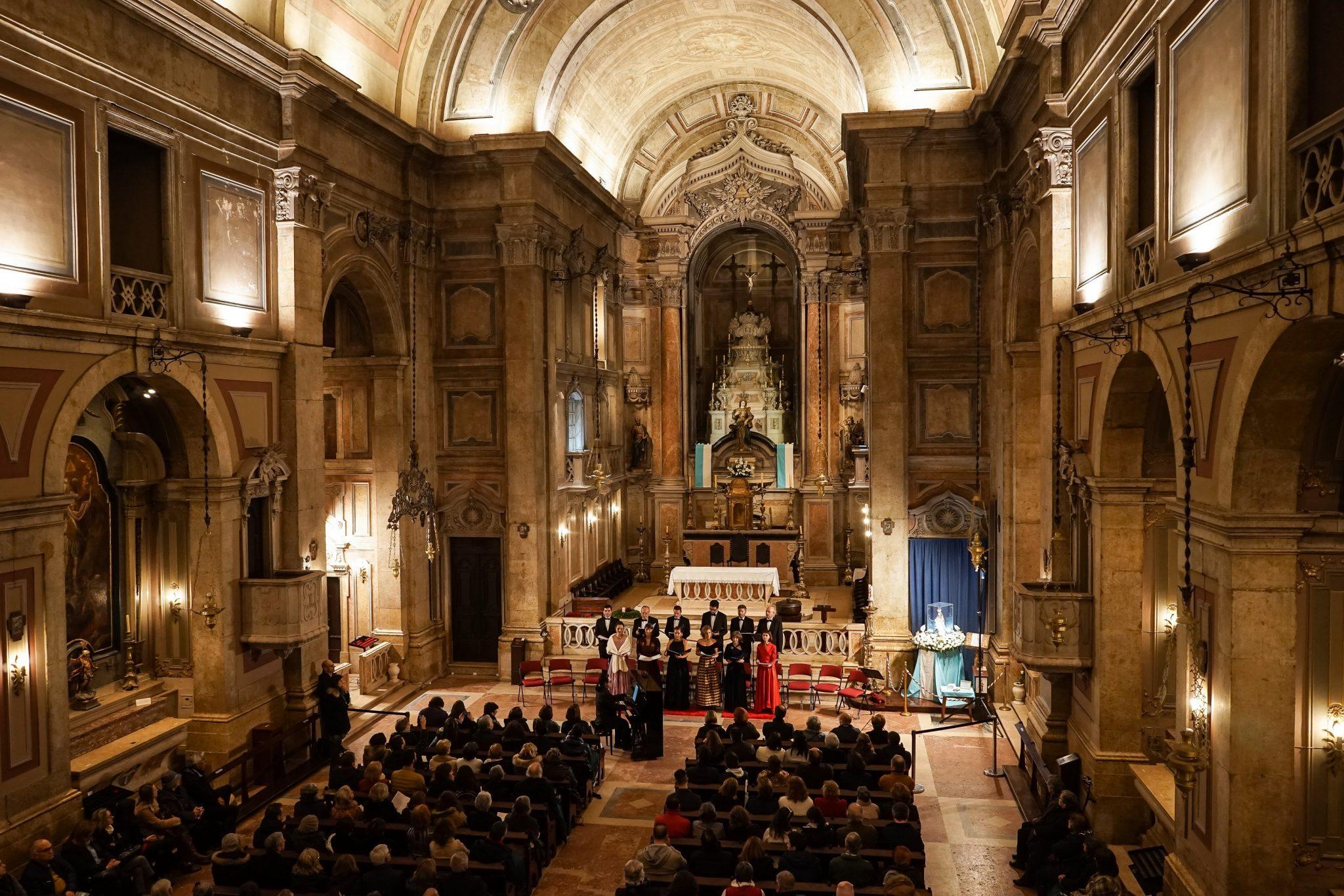 Interior da Igreja de Nossa Senhora do Amparo, com público sentado nos bancos a assistir a um concerto