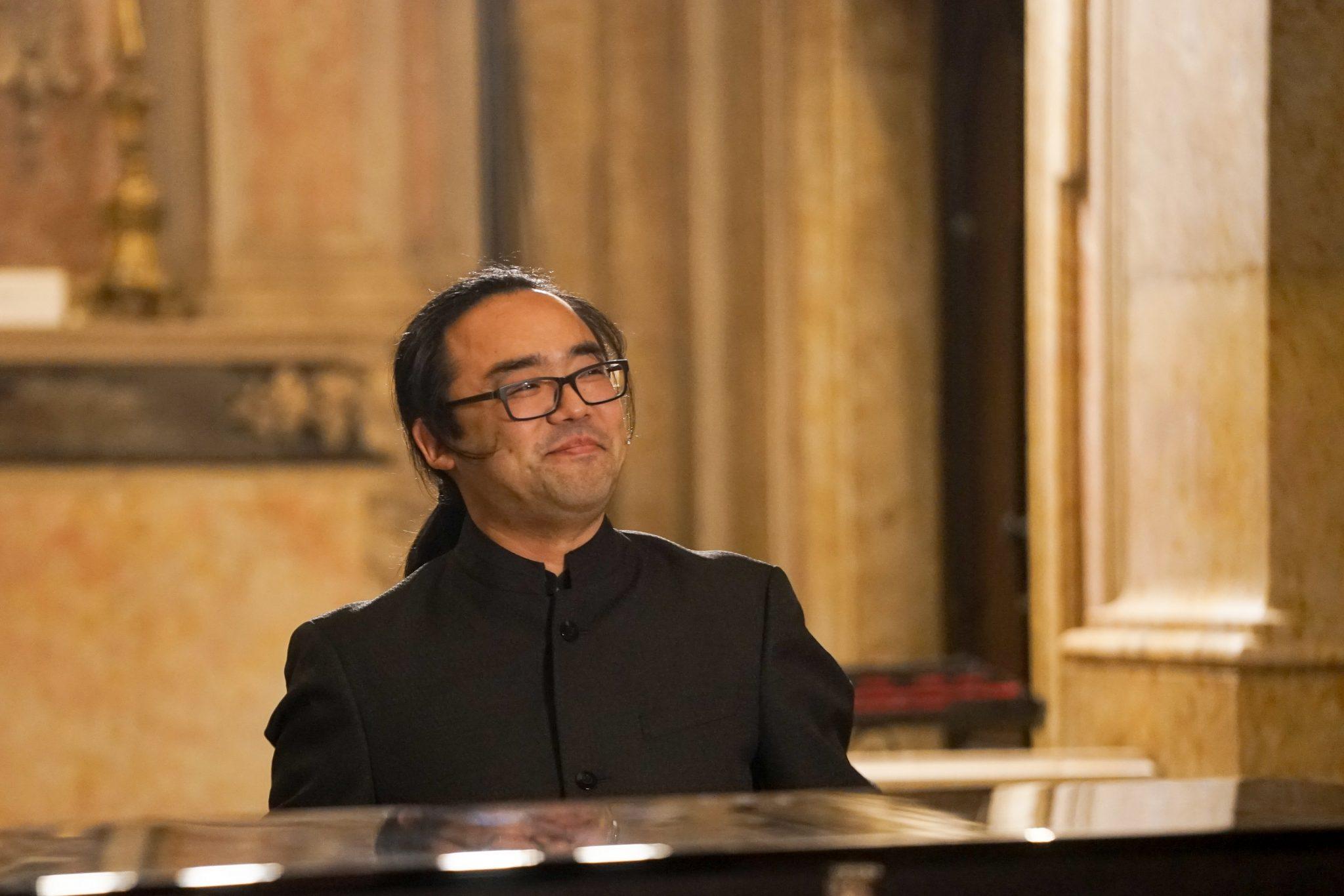 Homem, de traços asiáticos, sentado ao piano