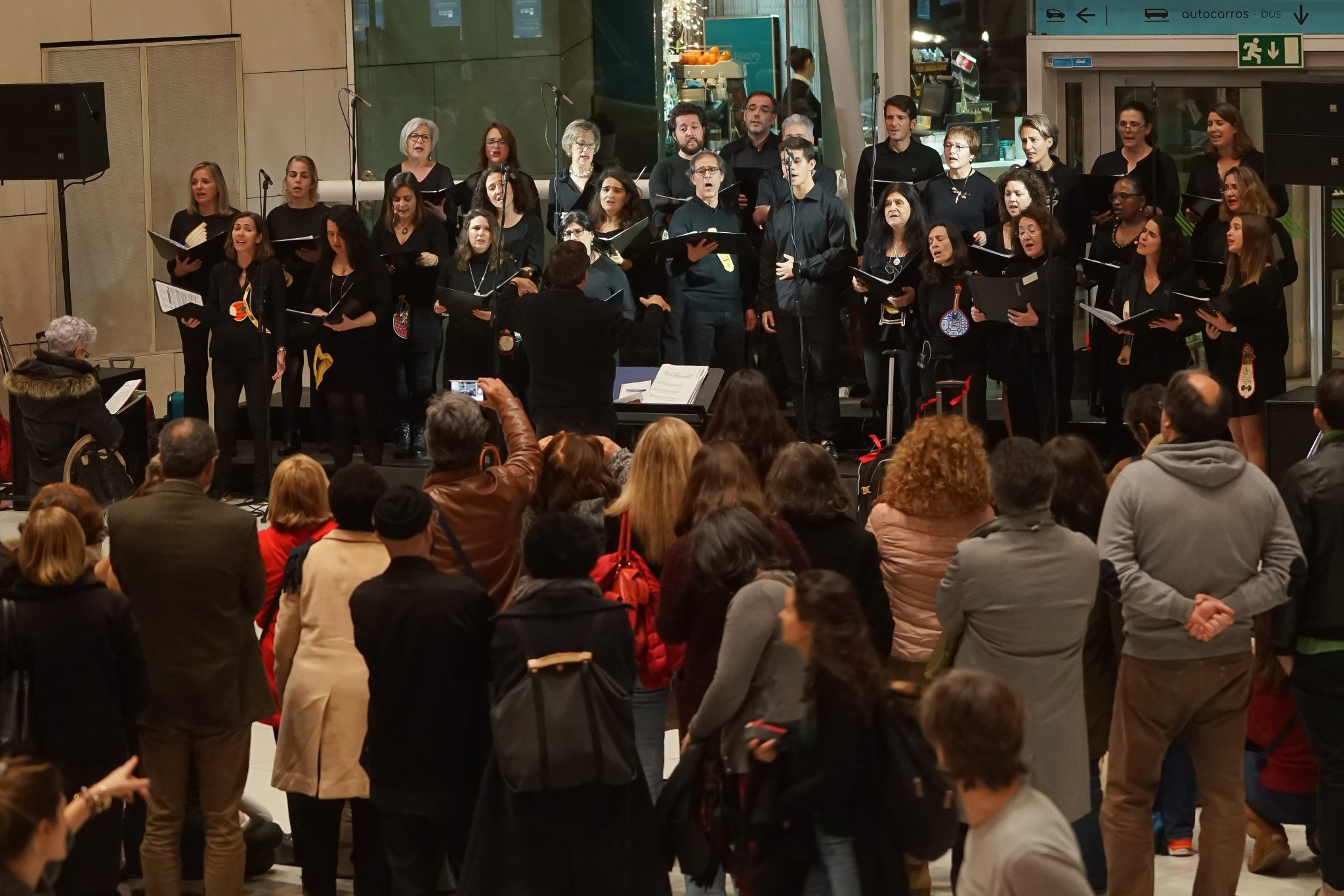 De frente para o observador, grupo de cantores durante actuação. De costas para o observador, público a assistir
